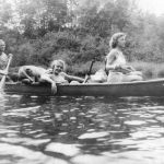 Canoeing, heritage photo of female campers paddling